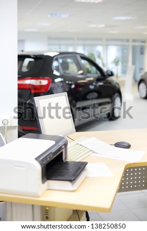 Computer, printer and documents on wooden desk and new car stands in office of car shop. Shallow depth of field. Focus on display. - stock photo