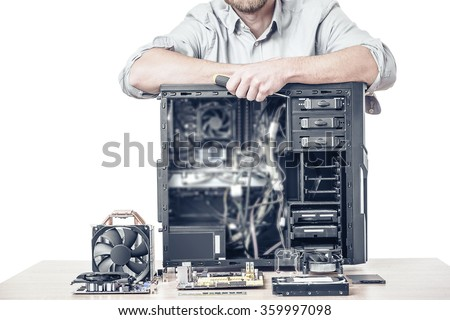 Computer repair concept. Master of computer repair put his hands on the disassembled computer system unit. Toned photo. - stock photo