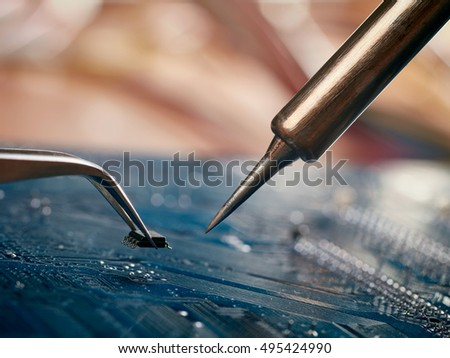 Computer repair concept. Tweezers with chip and soldering Iron