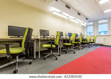 Computer room with green swivel chairs and fitted carpet - stock photo
