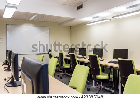 Computer room with green swivel chairs and whiteboard