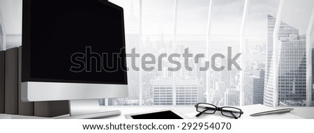 Computer screen against window overlooking city - stock photo