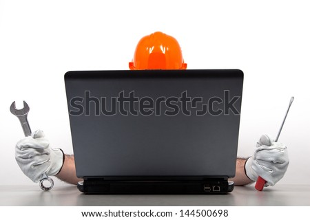 Computer specialist is ready for repairing damaged computer by hand tools - wrench and screwdriver.  - stock photo