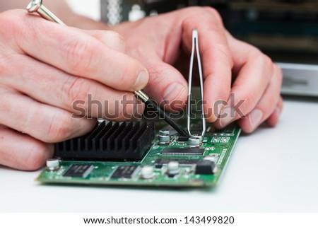 computer specialist use tweezers to repair circuit printed board - stock photo
