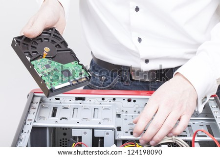 computer support engineer changing the hard drive of an office Computer. Studio shot on a white background. - stock photo