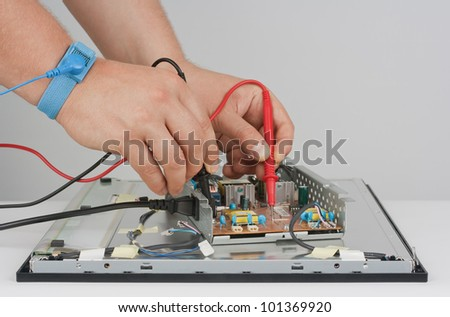 Computer support engineer repairing the power supply of LCD monitor. - stock photo