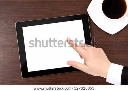 computer tablet and a cap of caffe on the table and hand of a businessman in a suit points to the screen