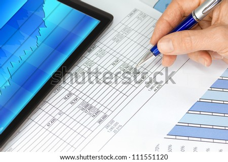 Computer Tablet Graphs Spreadsheet and Hand with Pen - stock photo