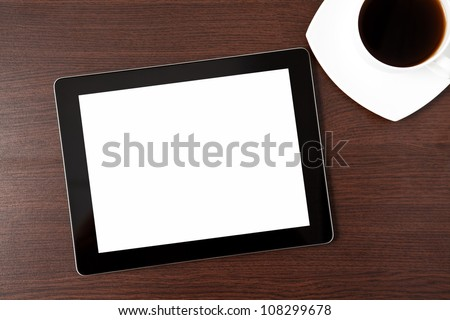 computer tablet touch computer gadget and a cap of coffee on the table of a businessman