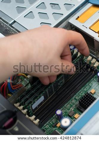 Computer technician installing RAM memory into motherboard. - stock photo