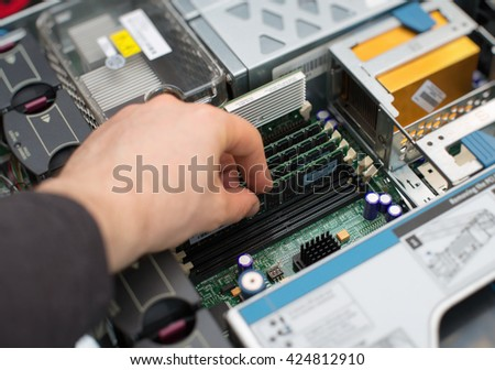 Computer technician installing RAM memory into motherboard. - stock photo