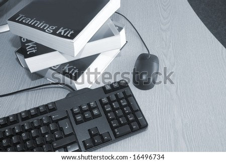 Computer training books with keyboard and mouse in college - stock photo