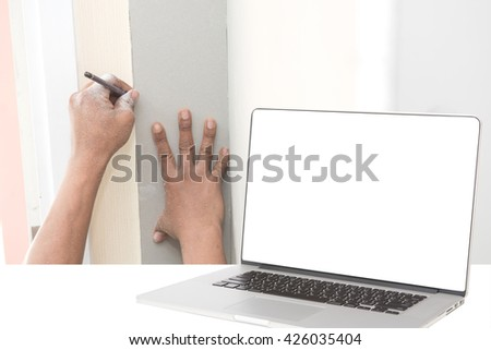 computer with blank screen and worker installing gypsum board