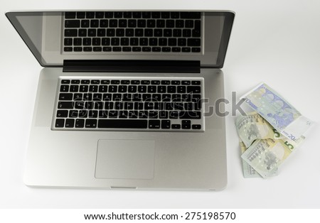 Computer with Euro money on a white background. - stock photo