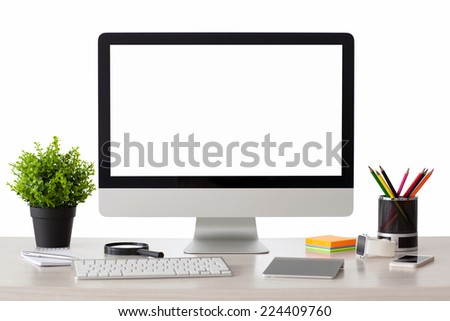 computer with isolated screen stands on the table in the office with phone and watch - stock photo