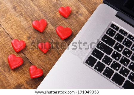 Computer with red hearts on table close up - stock photo