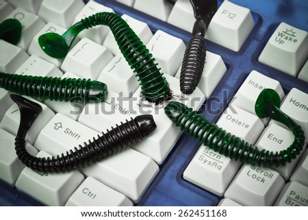 computer worm attacking computer system by penetrating a computer button on a keyboard - worm infection - stock photo