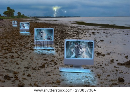 Computers on a stormy rocky shoreline with a man on the screens showing many emotions illustrating social media legal issues, computer bullying, computer problems, hacking malware security issues.  - stock photo