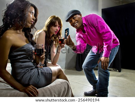 conceited man showing off muscular picture to women at nightclub - stock photo