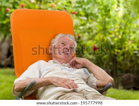 Conceived old man in sunbed in courtyard - stock photo