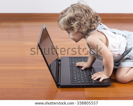 Concentrate baby looking at laptop computer. Little baby in front of screen of portable computer