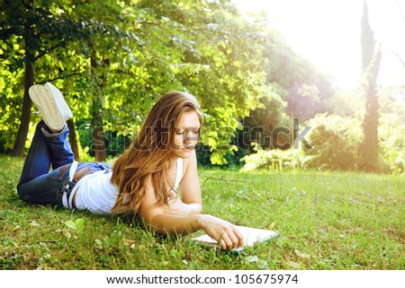 Concentrate beautiful young woman reading in park - stock photo