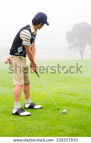 Concentrate golfer lining up his shot at the golf course - stock photo