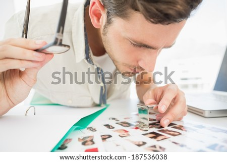 Concentrate male artist sitting at desk with photos in the office - stock photo