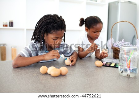 Concentrated Afro-american siblings painting eggs in the kitchen - stock photo