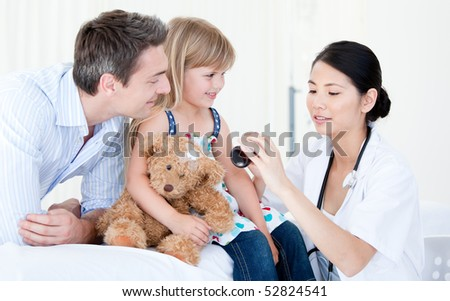 Concentrated asian female doctor giving syrup to a little girl against white background - stock photo