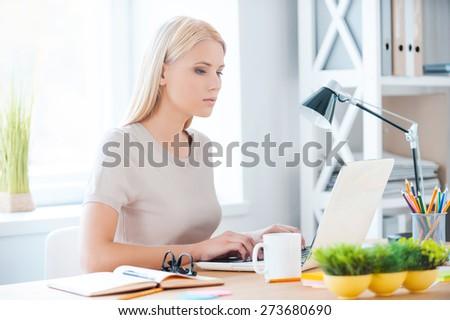 Concentrated at her work. Beautiful young woman working on laptop while sitting at her working place in office  - stock photo