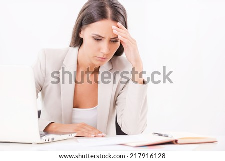 Concentrated at work. Depressed young businesswoman holding head in hand and looking at document laying at her table
