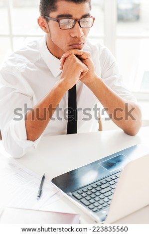 Concentrated at work. Handsome young Afro-American man formalwear holding hands on chin and looking at laptop while sitting at his working place - stock photo