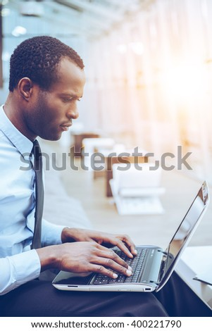 Concentrated at work. Side view of young and confident African man in formalwear working on laptop while sitting at his working place - stock photo