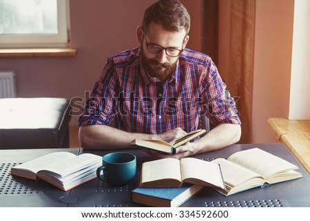 concentrated bearded man reading book - stock photo