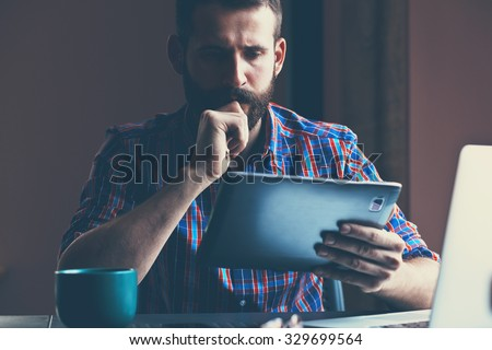 concentrated bearded man sitting with digital tablet and cup of coffee - stock photo