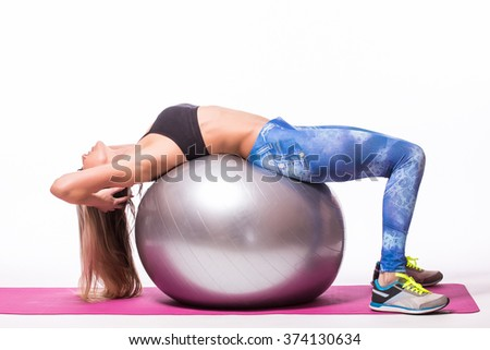 Concentrated beautiful fitness girl in sportwear doing sport with fitball over white background