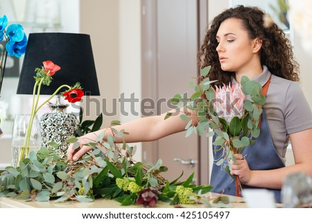Concentrated beautiful young woman florist making bouquet with fresh flowers in the shop