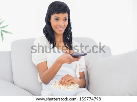 Concentrated black haired woman in white clothes watching tv while eating popcorn in a living room - stock photo