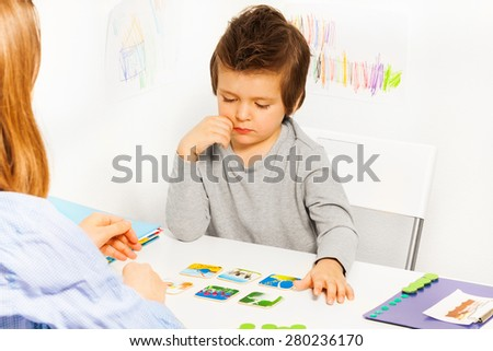 Concentrated boy plays developing game at  table - stock photo