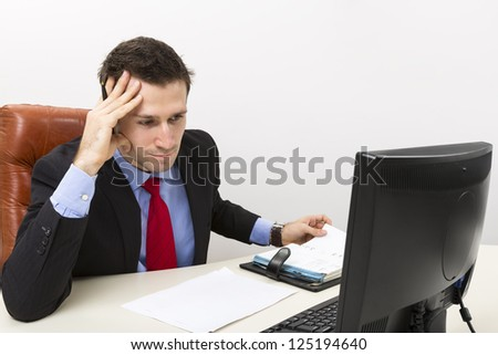 Concentrated business man in his office with right hand on his head. - stock photo