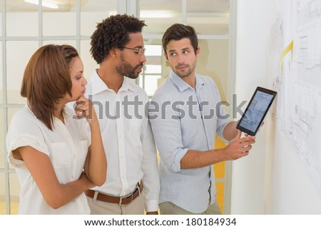 Concentrated business people using digital tablet in meeting at the office - stock photo