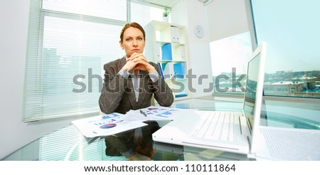 Concentrated business woman siting at workplace in office - stock photo