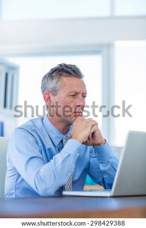 Concentrated businessman looking at laptop computer in office