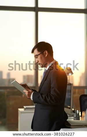 Concentrated businessman reading information on his tablet computer