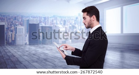 Concentrated businessman touching his tablet against city scene in a room - stock photo