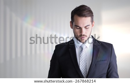 Concentrated businessman using magnifying glass against white curved room - stock photo