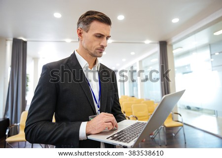 Concentrated businessman working with laptop in empty conference room