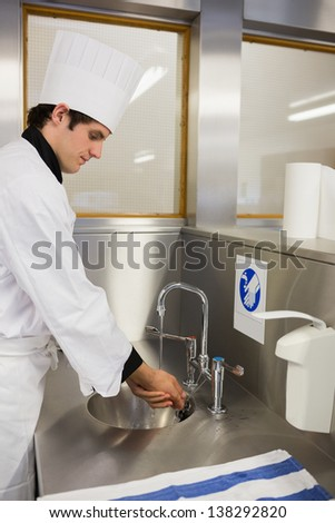 Concentrated chef washing hands in the restaurant
