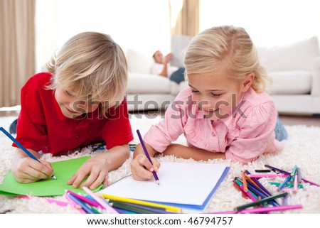 Concentrated children drawing lying on the floor in the living-room
